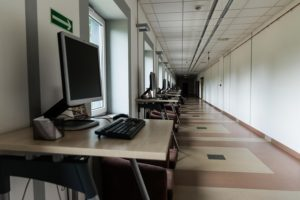 A row of computer workstations line a wall. There are no people in the picture.