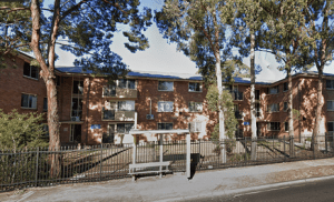 A group of red brick three storey apartments shaded by trees.