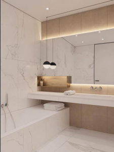 Pale marble tiles line the walls of this bathroom. There is one long shelf with a mirror behind. A bath with a hand held shower is fitted just above the bath rim.