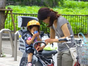 A young woman attends to a small child in a child seat on the back of the bicycle. The bike has a shopping basket.