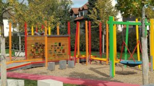 A play area showing brightly coloured poles and a boardwalk leading to equipment.