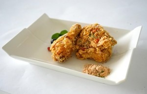 Three pieces of fried chicken are placed in a white cardboard box.