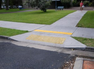 View of a kerb cut with yellow tactile markers on the kerb ramp.