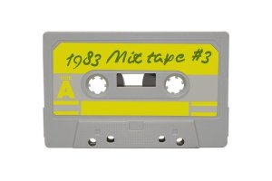 A grey coloured music cassette tape with a yellow label marked, '1983 Mix Tape #3.'