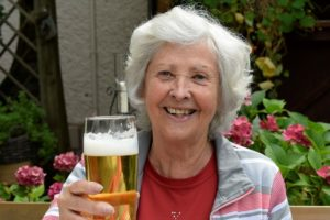 An older woman sits in a garden. She is holding a glass of beer and smiling. She looks happy.