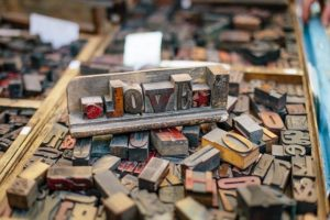 Realia: Woodtype blocks are piled on a table. The word 'love' , created from the typographic blocks stands on top.