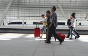 Passengers wheel their baggage on the train station platform. A very fast train is in the backgound.