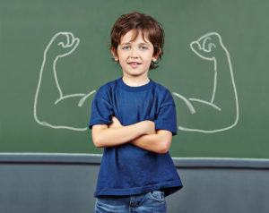 Image of a child with his arms crossed in front of a chalkboard with muscles drawn on it.