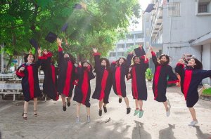 A row of female university graduates in gowns leap into the air with joy. The picture indicates their happiness in graduating.