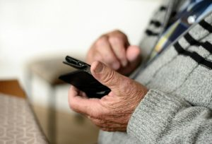 A pair of hands belonging to an older man hold a mobile phone.