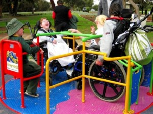 Three children, each a wheelchair user, are enjoying the spinner in the playground: a universal design.
