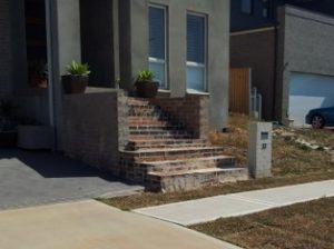 Front of a new house with 12 steps to the front door showing why construction code changes are needed..