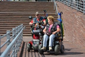 A woman in a powered wheelchair and a man in a mobility scooter enjoy the pathway.