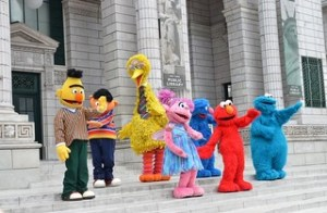 Sesame Street characters dancing in the street.