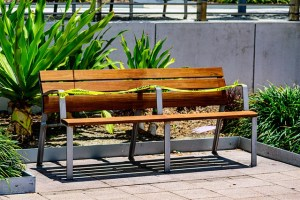 A street bench has yellow tape across it so that people cannot sit.