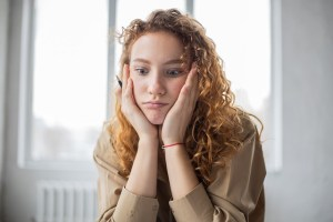 A young woman with long curly hair has her hands to her face and looks stressed.
