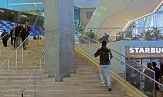 A long flight of stairs with a handrail leading to a large concrete column. A resource for architecture students.