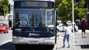 A young woman is ready to alight a bus in Auckland.