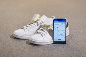 Two white shoes, a smartphone and the directional device.