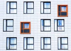 A white brick building with blue framed windows. Social value of good design.