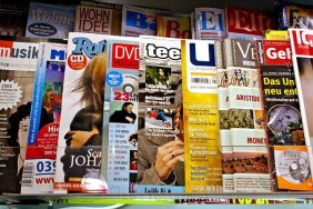 Magazine and news articles are laid out for viewing.
