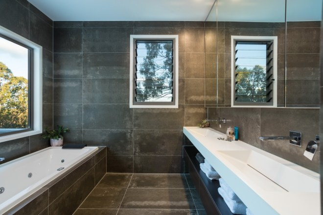 Bathroom design with dark tiles and floor and white bath and vanity bench.