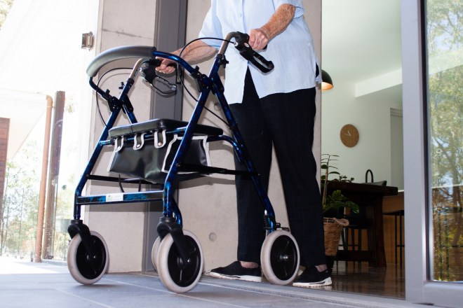 A person with a four-wheeled walker rolls over the level threshold.