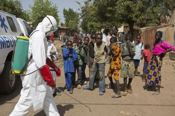 Children watch as a health worker sprays disinfectants outside a mosque in Bamako