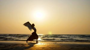 Silhouette of dancing woman with angel wings on the sandy beach