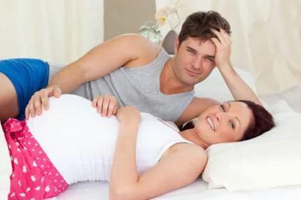 Donna incinta e compagno a letto