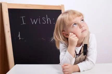 Bambina,con lavagna dietro di sè, pensa alla sua lista di desideri