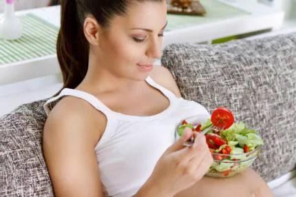 Donna incinta che mangia insalata