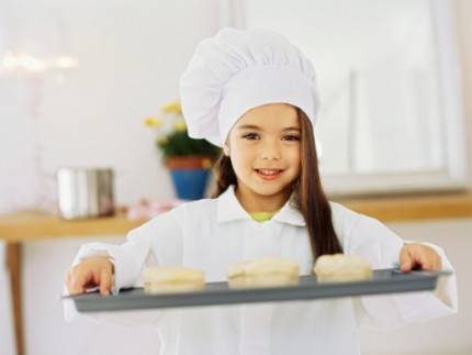 Bambina vestita da chef mentre porta un vassoio con dolci