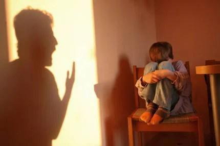 Bambino rannicchiato su una sedia e ombra di un uomo che gli urla contro