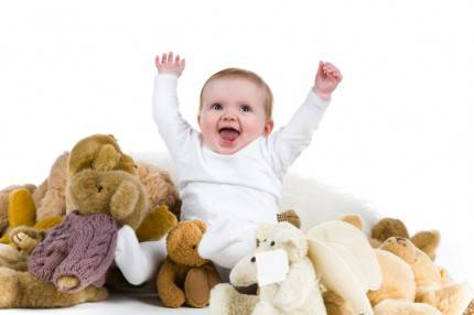 neonato sorride in mezzo a giocatt