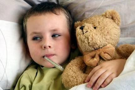 Un bimbo è a letto e misura la febbre mentre stringe il suo orsacchiotto