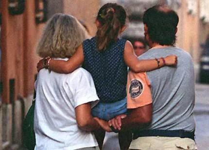 Mamma e papà tengono in braccio la figlia sostenendosi a vicenda