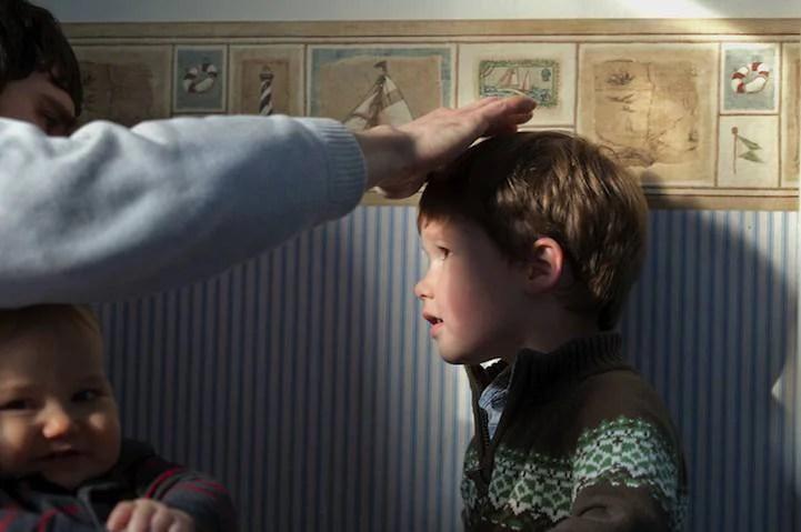 Padre spiega al figlio come toccare delicatamente il fratello più piccolo