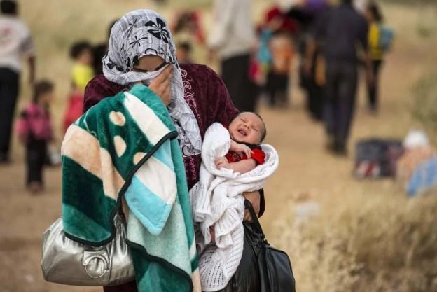 madre con chador e neonato tra le braccia, in situazione di miseria