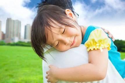 Una bambina sorride perché viene abbracciata dal suo papà