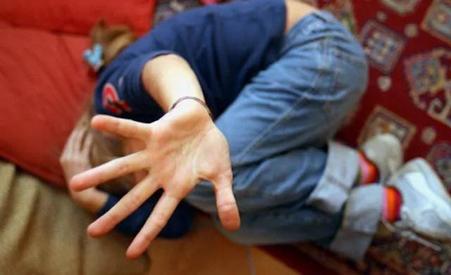 Un bambino cerca di proteggersi da qualcuno che vuole fargli del male