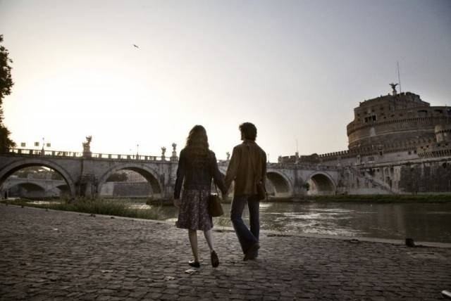 Un uomo e una donna passeggiano mano nella mano