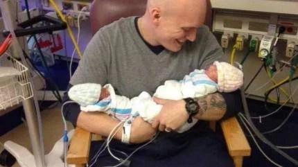 padre con in braccio le sue gemelle neonate