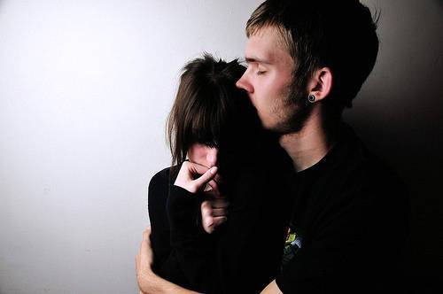 Un uomo bacia la propria donna