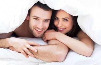 Una donna e un uomo sono sorridenti sotto le coperte