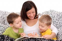 mother and two sons reading book in bed