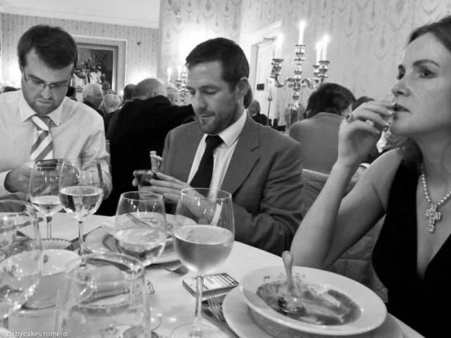 persone a cena giocano col cellulare
