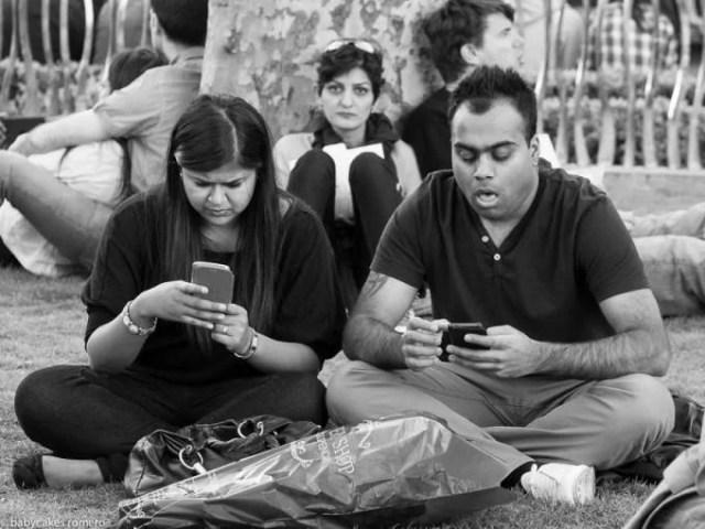 persone al parco guardano telefono