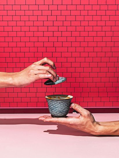 Hand holding a decorative latte cup against an illustrative image of a brick wall