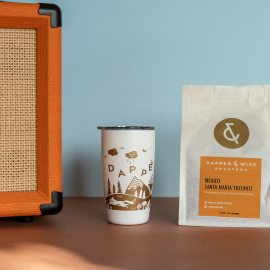 Dapper & Wise coffee and tumbler next to an amp